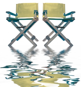 vintage movie directors chairs with reflection in the water